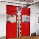 Puerta rápida Speedsystem en acero inoxidable, con encajes para transportadores aéreos.
